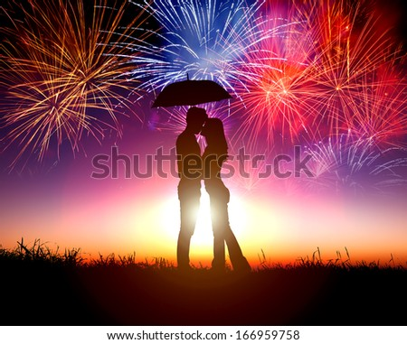 Couple kissing under umbrella with firework in the sky - stock photo