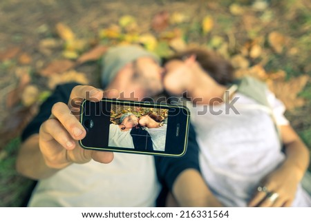Couple kissing while taking a selfie with smart phone - autumn,people,love,technology,lifestyle concept - stock photo