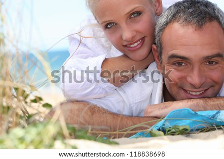 Couple, laid down at the beach - stock photo