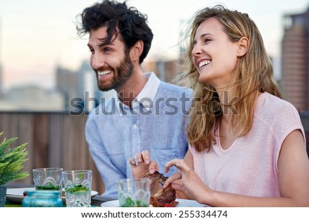 Couple laughing having fun together with beer outdoors - stock photo