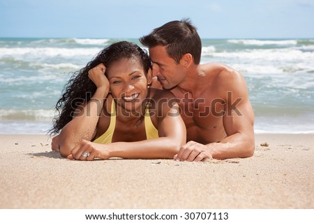 Couple laying at beach on sand, having fun