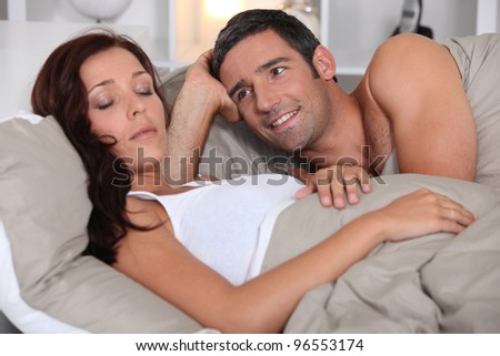 Couple laying in bed - stock photo