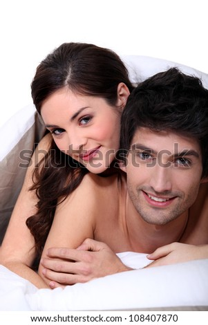Couple laying in their bed - stock photo