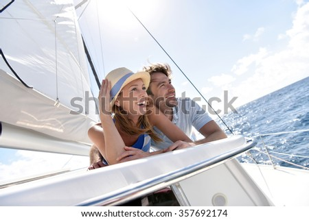 Couple laying on a sailboat deck during cruise - stock photo