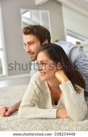 Couple laying on carpet in living room