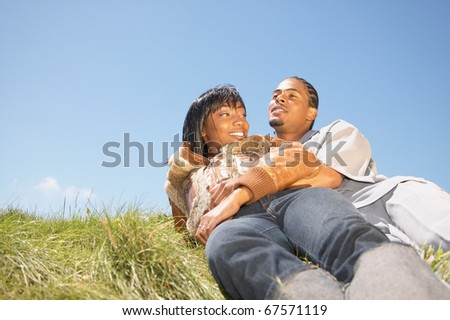 Couple laying on grass together - stock photo