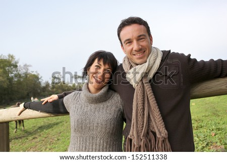 Couple leaning against fence in field - stock photo
