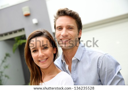 Couple leaning on fence in front of home