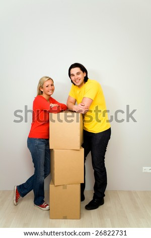 Couple leaning on packing boxes - stock photo