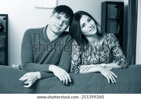 Couple leaning over their couch - stock photo