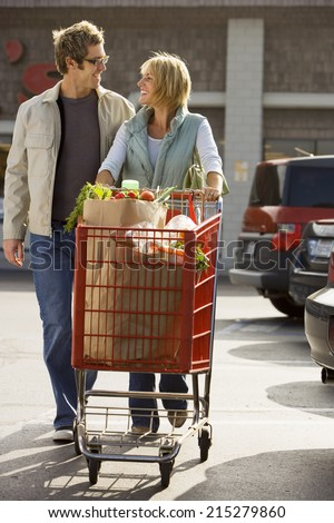Couple leaving supermarket, woman pushing shopping trolley in car park, smiling, front view - stock photo