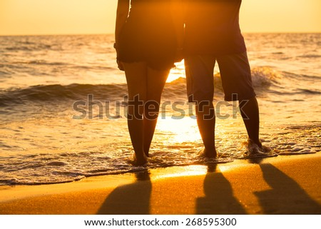 Couple legs silhouette falling in love at sunset on the beach with the sun in the background - stock photo