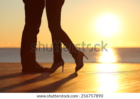 Couple legs silhouette falling in love hugging at sunset on the beach with the sun in the background - stock photo