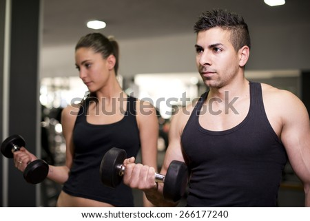 Couple lifting dmbbells weights training biceps at gym with ambient light - stock photo