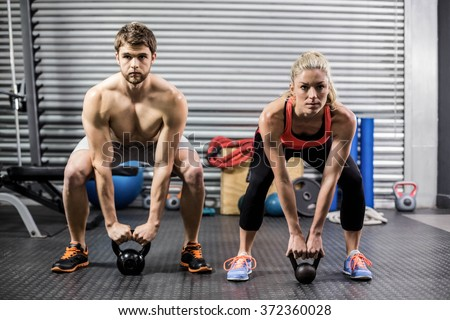 Couple lifting dumbbells together at crossfit gym - stock photo