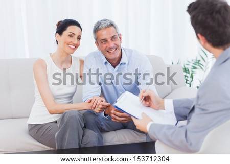 Couple listening to salesman holding contract at home on couch
