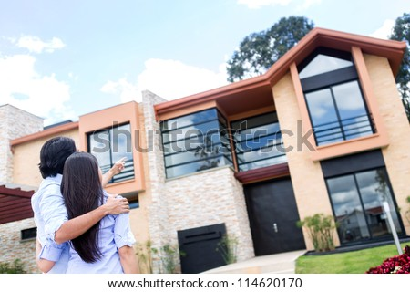 Couple looking at a beautiful house to buy - stock photo