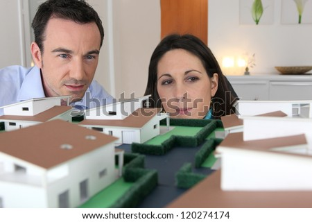 Couple looking at a model of a housing estate