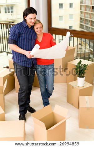 Couple looking at blueprints in new house - stock photo