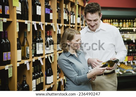 Couple Looking at Bottle of Wine