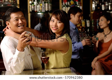 Couple looking at camera, woman hugging man