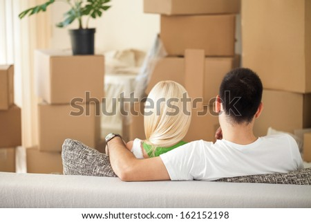 Couple looking at cardboard boxes in her new home, back view - stock photo