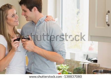 Couple looking at each other and drinking wine in kitchen - stock photo