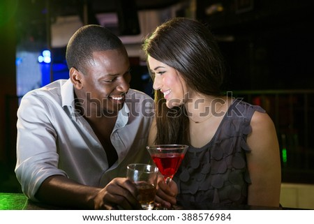 Couple looking at each other and smiling while having drinks at bar - stock photo