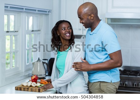 Couple looking at each other in kitchen