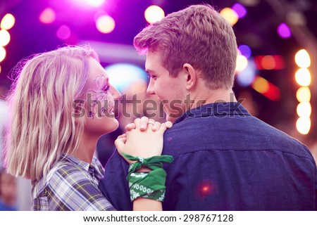 Couple looking at each other in the crowd at music festival - stock photo