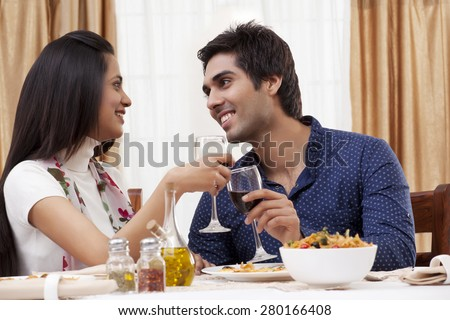 Couple looking at each other while clinking wine glass at restaurant - stock photo