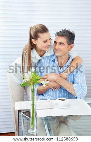 Couple looking at each other while embracing by a table
