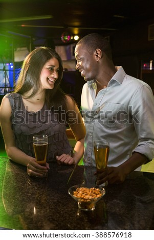 Couple looking at each other while having beer at bar counter in bar - stock photo