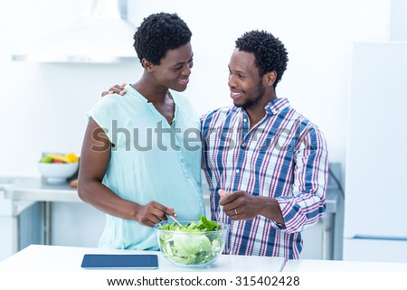 Couple looking at each other while having salad at home