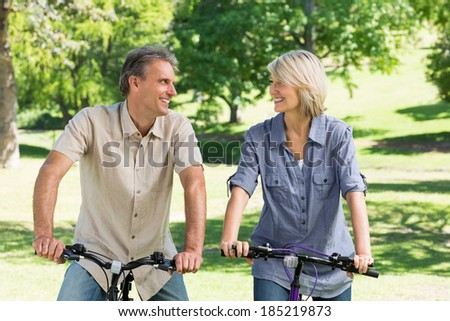 Couple looking at each other while riding bicycles in park