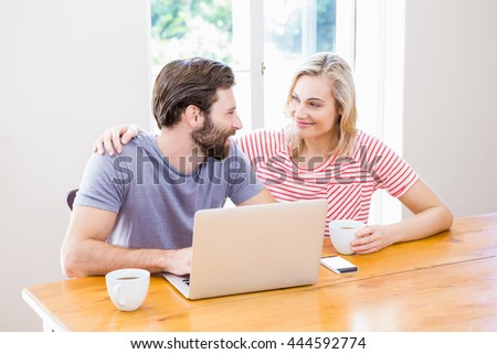 Couple looking at each other while using laptop and holding a coffee cup at table - stock photo