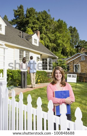 Couple looking at house with real estate agent - stock photo