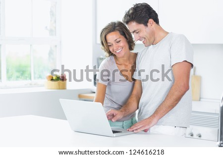 Couple looking at laptop in kitchen - stock photo
