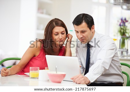 Couple Looking at Laptop Over Breakfast