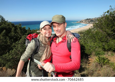 Couple looking at map on a hiking day - stock photo