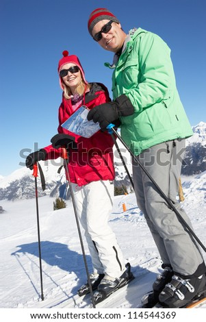 Couple Looking At Map Whilst On Ski Holiday In Mountains