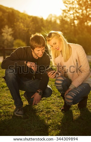 Couple looking at phone. Beautiful couple laughing while looking at phone. - stock photo