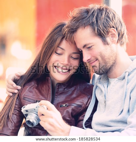 Couple looking at pictures on camera. Beautiful young lovers having fun together outside looking at photos on vintage retro camera. Interracial couple, Asian woman, Caucasian man. - stock photo