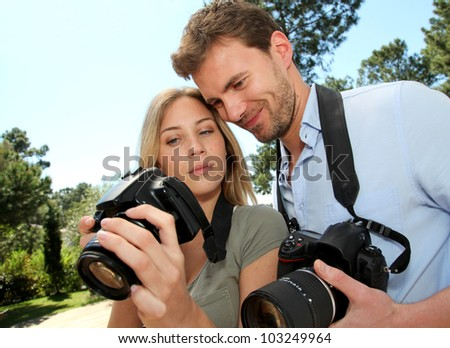 Couple looking at pictures through camera screen - stock photo