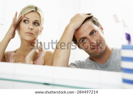 Couple Looking At Reflections In Mirror For Signs Of Ageing - stock photo