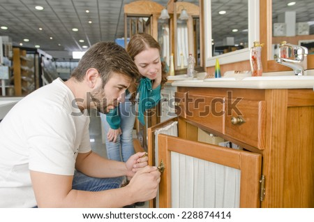 Couple looking at sink in furniture shop for home remodel - stock photo