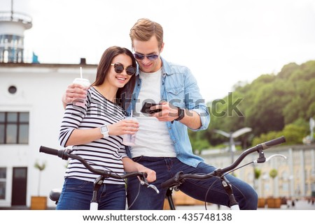 Couple looking at smartphone and drinking - stock photo