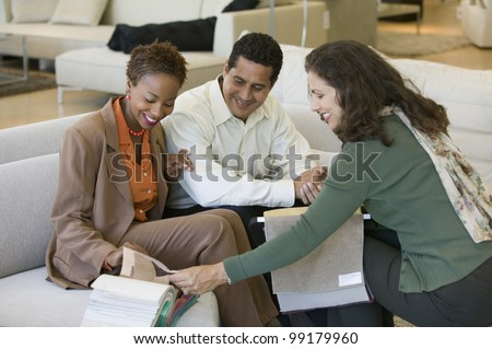 Couple Looking at Swatches With Saleswoman - stock photo