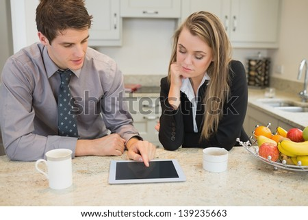 Couple looking at tablet pc with coffee in kitchen