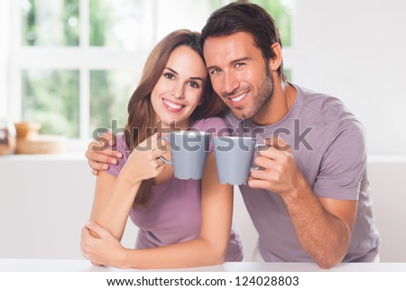 Couple looking at the camera with a coffee and smiling